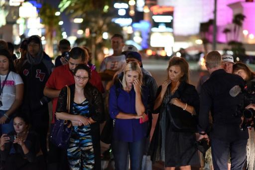 Des personnes se recueillent devant un mémorial près de l'hôtel Mandalay Bay après une fusillade meurtrière, le 3 octobre 2017 à Las Vegas © Robyn Beck AFP