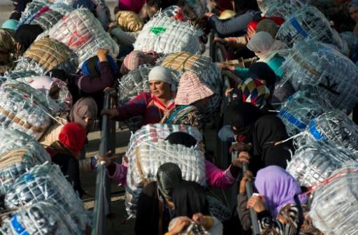 """Les """"femmes-mulets"""" chargent d'imposants sacs rectangulaires accrochés à l'aide de cordes, puis récupèrent un ticket mentionnant le montant qu'elles encaisseront une fois leur mission accomplie. © FADEL SENNA AFP"""