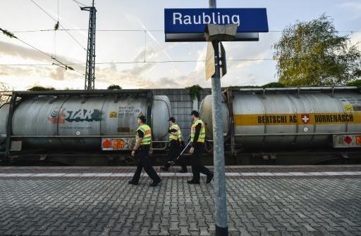 Un policier fait sortir de dessous un train une jeune fille somalienne de 15 ans à la gare de Raubling en Allemagne, le 24 août 2017 © Guenter SCHIFFMANN AFP/Archives