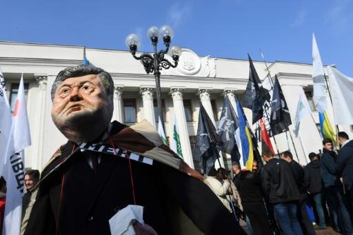 Un manifestant porte un masque représentant le président ukrainien Petro Porochenko, le 17 octobre 2017 à Kiev © Sergei SUPINSKY AFP