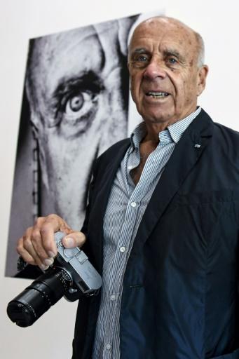 """Le photographe américain Ralph Gibson devant l'affiche de l'exposition """"La Trilogie, 1970-74"""" à Montpellier, le 17 octobre 2017   © PASCAL GUYOT AFP"""