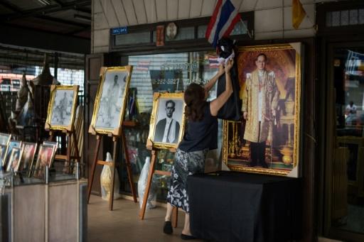 La propriétaire d'une boutique à Bangkok, Somsree, fixe un tissu noir sur le portrait du défunt roi thaïlandais Bhumibol, le 19 octobre 2017 © Roberto SCHMIDT AFP
