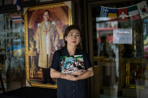 La propriétaire d'une boutique à Bangkok, Somsree, montre une photo du défunt roi thaïlandais Bhumibol, le 19 octobre 2017 © Roberto SCHMIDT AFP