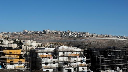 Des immeubles en construction dans la colonie israélienne de Pisgat Zeev, en face du Mur séparant Jérusalem de la ville de Ramallah (en arrière-plan), en Cisjordanie occupée, le 26 octobre 2017 © THOMAS COEX AFP