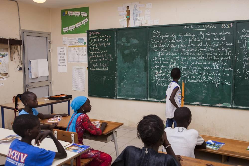 Scène d'une salle de classe en plein travail, à M'Bissao. ©  Martin Dixon
