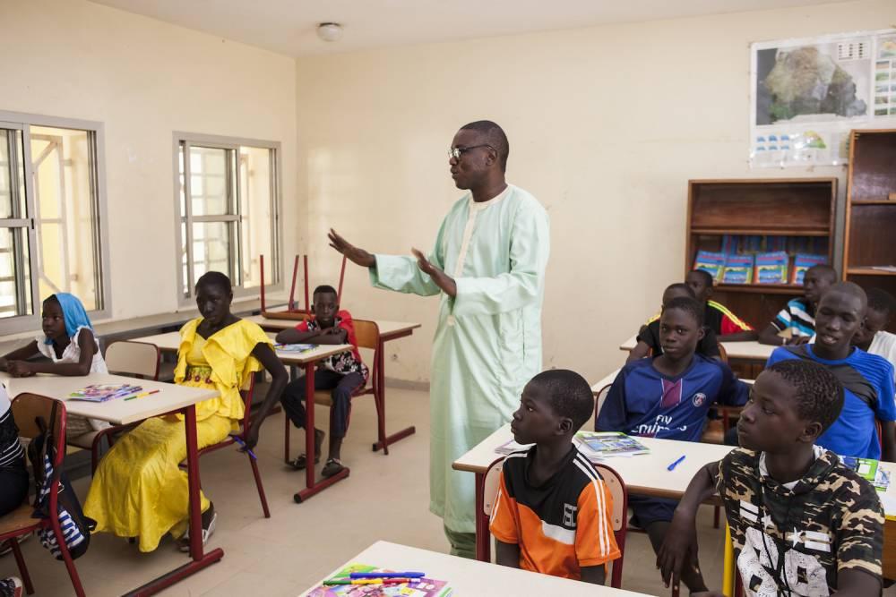 Le directeur de l'école de M'Bissao enseigne aussi à une classe de primaires.  ©  Martin Dixon