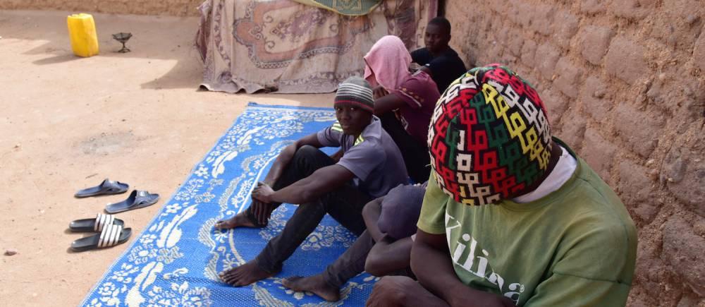 """Des migrants ouest-africains dans la cour d'un """"ghetto"""" à Agadez en avril 2017.  ©  ISSOUF SANOGO / AFP"""