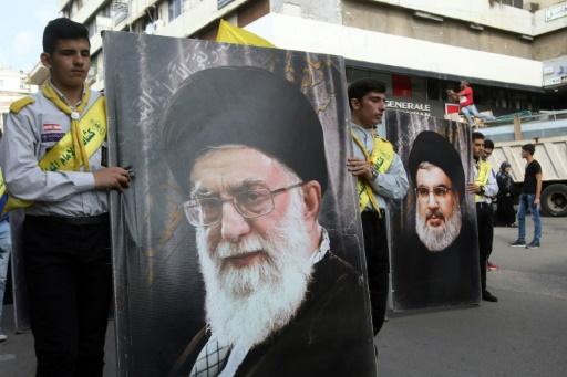 Des partisans du Hezbollah arborent des posters du chef du mouvement Hassan Nasrallah (D) et du guide suprême d'Iran Ali Khamenei (G) lors de funérailles de combattants tués en Syrie, à Nabatiyé dans le sud du Liban le 8 novembre 2017 © Mahmoud ZAYYAT AFP/Archives