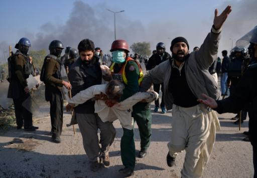 Des manifestants islamistes transportent un blessé lors de heurts avec la police pakistanaise, le 25 novembre 2017 à Islamabad © AAMIR QURESHI AFP