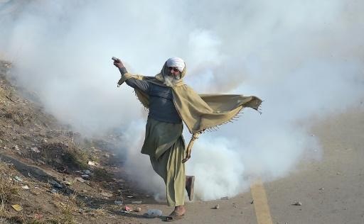 Un manifestant islamiste pakistanais renvoie une grenade lacrymogène sur les forces de l'ordre samedi 25 novembre 2017 à Islamabad © AAMIR QURESHI AFP