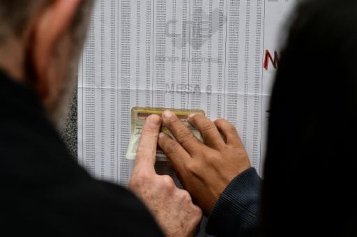 Des électeurs contrôlent les listes électorales lors du scrutin pour les municipales, le 10 décembre 2017 à Caracas © FEDERICO PARRA AFP