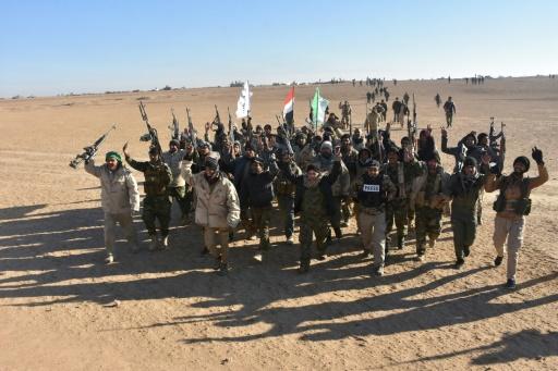 Des membres du Hachd al-Chaabi célèbrent après l'annonce de la victoire contre le groupe Etat islamique (EI), non loin de la frontière irako-syrienne, le 9 décembre 2017 © STRINGER AFP