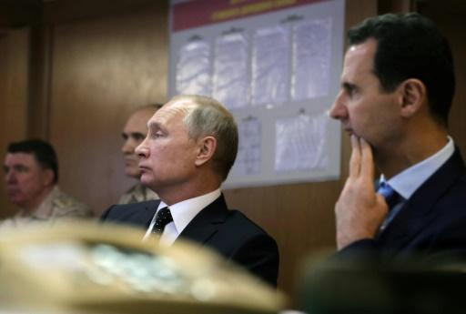 Le président russe Vladimir Poutine (g) et son homologue syrien Bachar al-Assad, lors d'une réunion avec des officiers russes à Hmeimim (nord-ouest de la Syrie), le 11 décembre 2017 © Mikhail KLIMENTYEV POOL/AFP