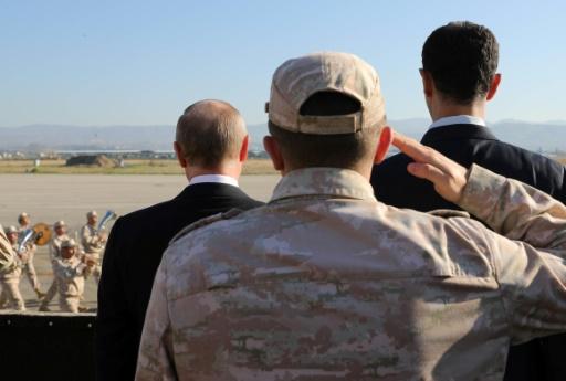 Vladimir Poutine (g), le président syrien Bachar al-Assad (R), assistent à un défilé militaire sur la base aérienne de Hmeimim (nord-ouest) de la Syrie, le 11 décembre 2017 © Mikhail KLIMENTYEV POOL/AFP