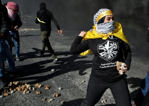 Une Palestinienne jette des pierres aux soldats israéliens à Ramallah, le 11 décembre 2017, pour protester contre la décision américaine de reconnaître Jérusalem comme capitale d'Israël © ABBAS MOMANI AFP