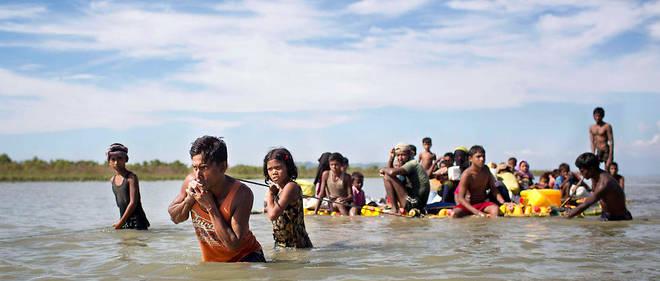Des Rohingyas, deconfession musulmane, traversent la rivère Naf quisépare leur pays, laBirmanie, du Bangladesh.