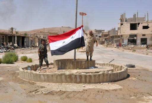 Des combattants syriens pro-gouvernementaux hissent un drapeau syrien à Al-Soukhnah, en Syrie libéré  du groupe Etat islamique, le 13 août 2017 © STRINGER AFP/Archives