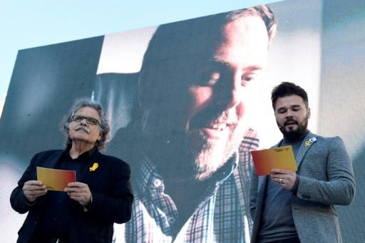 Des parlementaires d'Esquerra Republicana de Catalunya, Joan Tarda (à gauche) et Gabriel Rufian, s'expriment devant un portrait géant de l'ex-vice président catalan incarcéré Oriol Junqueras lors d'un meeting de campagne à Barcelone, le 16 décembre © JAVIER SORIANO AFP