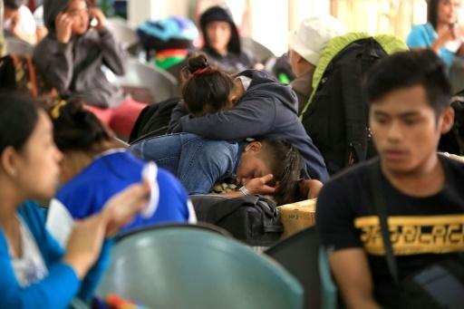 Des passagers bloqués par la tempête Kai-Tak attendent dans le port de Matnog, aux Philippines, le 17 décembre © CHARISM SAYAT AFP