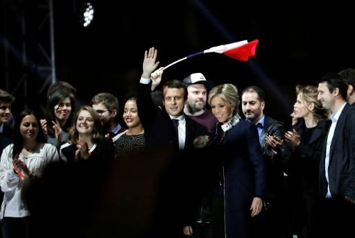 Emmanuel Macron accompagné de sa femme Brigitte salue la foule devant le Musée du Louvre au soir de son élection à la présidence de la République, le 7 mai 2017 © Patrick KOVARIK AFP/Archives