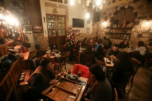 De jeunes Syriens discutant, jouant au backgammon et écoutant du jazz au café Zeriab à Damas le 17 décembre 2017 © Youssef KARWASHAN AFP