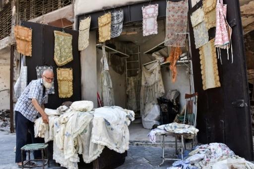 Mohammad Chawach dispose ses nappes dans sa boutique du souk d'Alep le 22 juillet 2017 © George OURFALIAN AFP