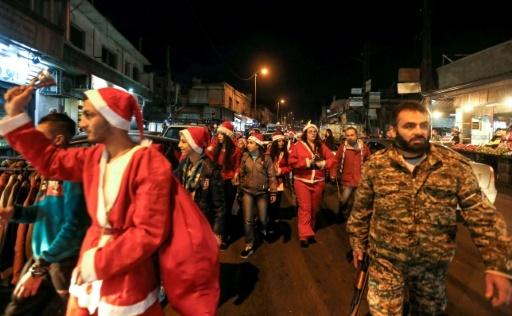 Des Syriens habillés en Père Noël déambulent dans les rues de Damas escortés par des militaires le 24 décembre 2017 © LOUAI BESHARA AFP