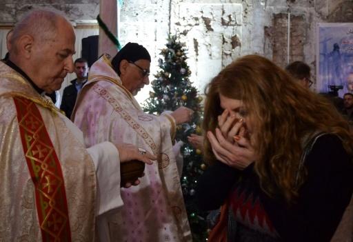 Une Irakienne reçoit l'eucharistie lors de la messe de Noël à l'église Saint Paul à Mossoul le 24 décembre 2014 © Ahmad MUWAFAQ AFP