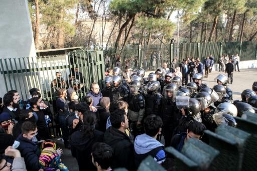 Etudiants manifestant contre le gouvernement face à des forces de l'ordre devant l'université de Téhéran le 30 décembre 2017 © STR AFP