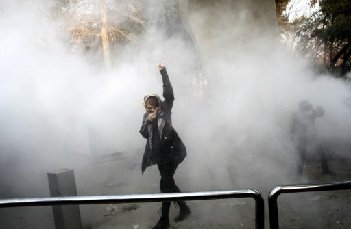 Une Iranienne lève le poing dans la fumée des gaz lacrymogènes lors d'une manifestation à Téhéran, le 30 décembre 2017 © STR AFP