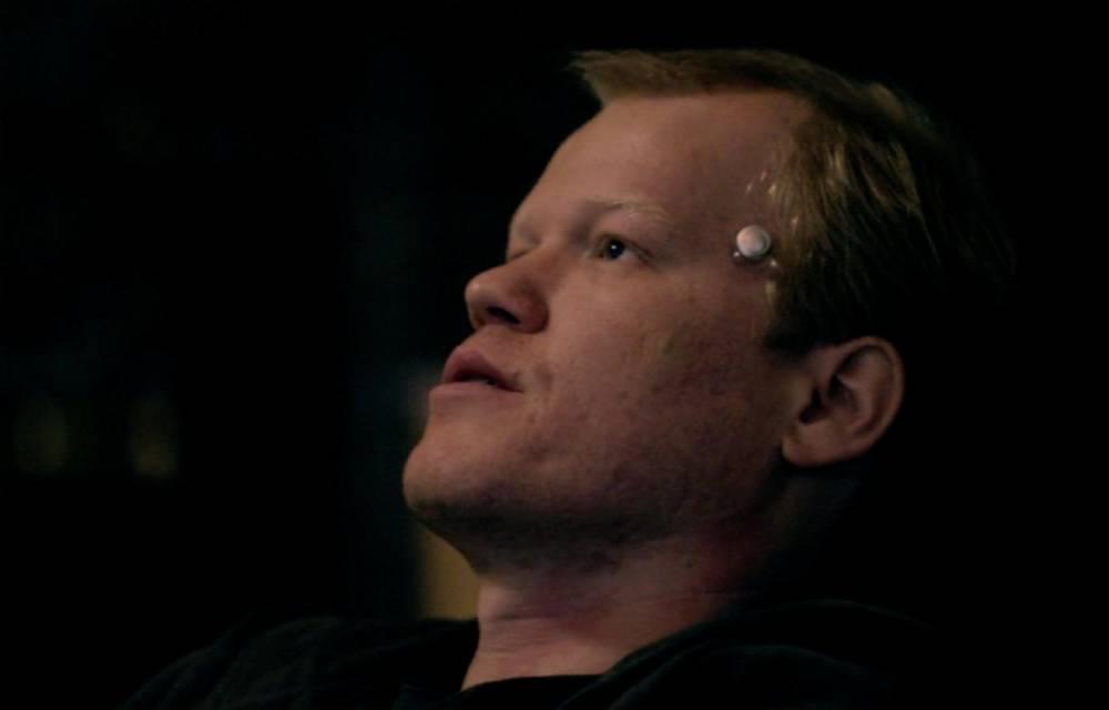Robert Daly, personnage principal de l'épisode, place sa place contre sa tempe pour entre dans le monde virtuel qu'il a créé ©  Netflix