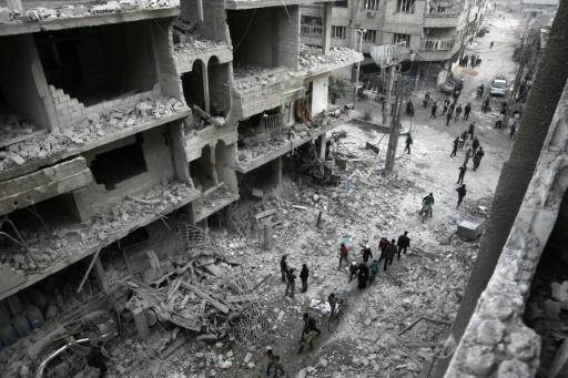 Des civils face aux dégâts causés par des raids aériens de l'aviation syrienne et de son allié russe à Hamouria, dans la Ghouta orientale, enclave rebelle à l'est de Damas, le 6 janvier 2018 © ABDULMONAM EASSA AFP