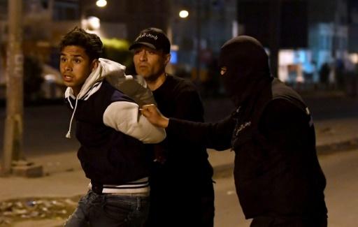 Des membres des forces de sécurité tunisiennes arrêtent un homme à Ettadhamen, dans la banlieue de Tunis le 10 janvier 2018 © FETHI BELAID AFP