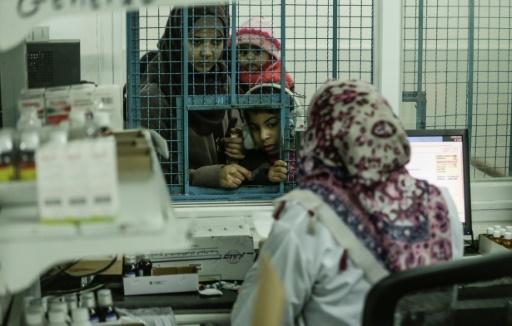Une famille palestinienne récupère des médicaments dans une clinique tenue par l'agence onusienne UNRWA, le 17 janvier 2018 dans la bande de Gaza © MAHMUD HAMS AFP