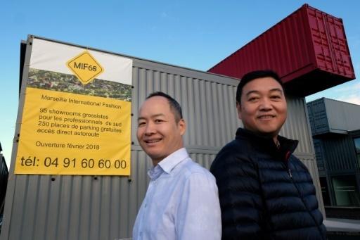 Le président du MIF68 Chen Dingguo (dr) et un client Zheng Yinde (g) lors d'une visite du Marseille International Fashion Center, le 17 janvier 2018 © BORIS HORVAT AFP