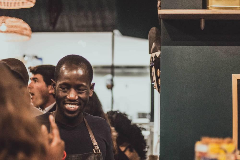 Fousseyni Djikine , en plein discussion, et entouré de visiteurs dans le restaurant-épicerie BMK.  ©  Djikine