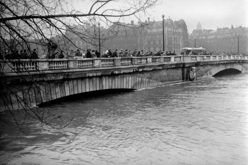 Des Parisiens regardent la crue de la Seine et la statue du Zouave du Pont de l'Alma, le 23 janvier 1955 © - AFP/Archives