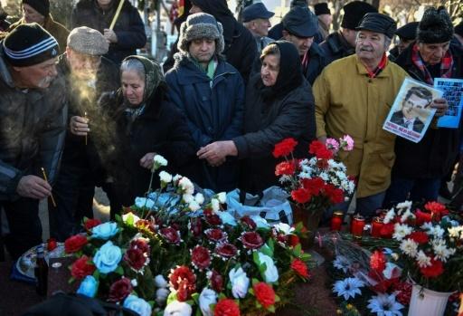 Des nostalgiques allument des chandelles sur la tombe de l'ancien dicateur roumain Nicolae Ceaucescu et de son épouse Elena au cimetière Ghencea de Bucarest, le 26 janvier 2018 © Daniel MIHAILESCU AFP