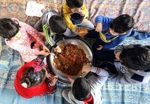Des enfants mangent un couscous à Tripoli, en Libye, le 6 février 2018 © MAHMUD TURKIA AFP