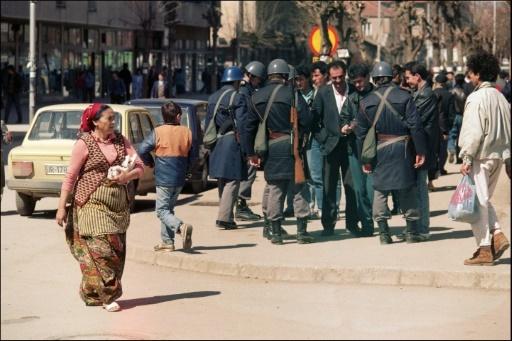 Une photo prise le 31 mars 1989 à Pristina d'une femme albanaise passant devant des policiers effectuant des vérifications de papiers © MICHEL GANGNE AFP/Archives