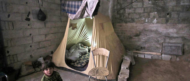 Un enfant syrien se tient à côté d'une tente installée dans un sous-sol où une famille a trouvé refuge après que sa maison a été détruite à Mudayra, dans la Ghouta orientale, le 28 janvier 2018.
