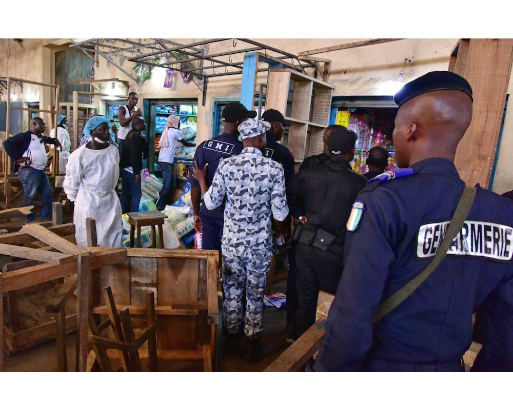 Des gendarmes ivoiriens et des employés du ministère de la Santé traquent des médicaments falsifiés au marché d'Adjamé, en Côte d'Ivoire.  ©  ISSOUF SANOGO / AFP