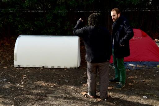 """L'ingénieur Geoffroy de Reynal (à droite) parle avec un sans-abri près d'un """"Iglou"""" de sa conception © NICOLAS TUCAT AFP"""