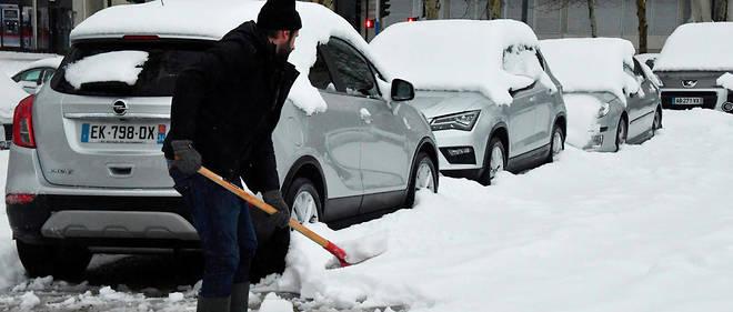 Jeudi matin, un automobiliste tente de déneiger sa voiture garée dans la rue à Montpellier.