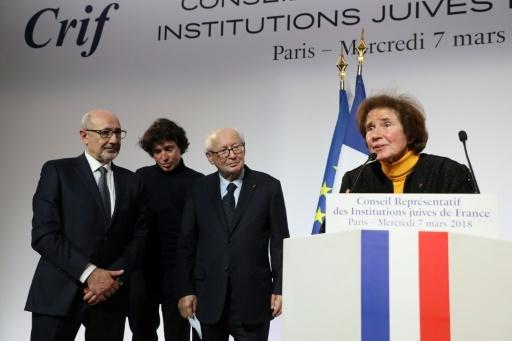 Beate Klarsfeld à la tribune lors du diner du Crif, s'exprime devant son mari Serge Klarsfeld (3è d), son fils Arno Klarsfeld (c) et le président du Crif Francis Kalifat (g), le 7 mars 2018, à Paris © LUDOVIC MARIN POOL/AFP