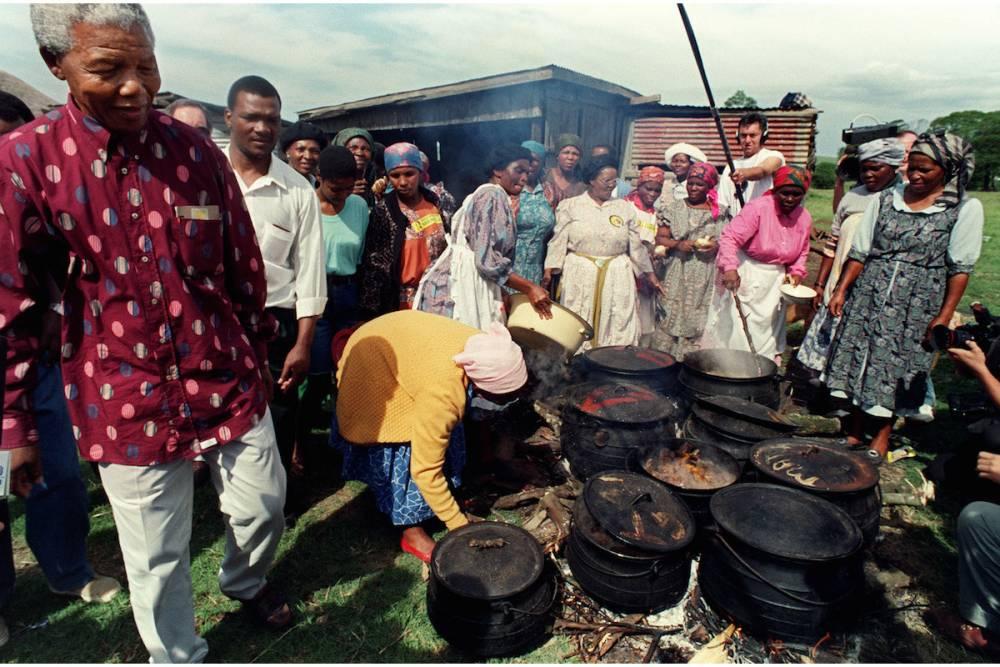 Nelson Mandela lors de la première campagne électorale ouverte du pays. Le dirigeant du Congrès national africain (ANC) passe devant le déjeuner des femmes lors de sa tournée, le 5 mars 1994 à Maekwezen. ©  AFP/Walter Dhladhla
