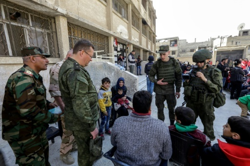 Photo de soldats syriens et russes échangeant avec des civils évacués de la Ghouta orientale, dans la cour d'une école située à proximité du point de passage de Wafidine, le 13 mars 2018 © LOUAI BESHARA AFP