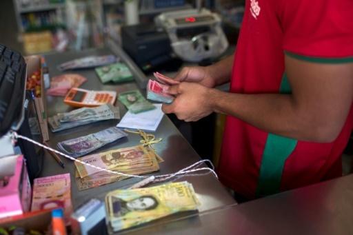 Un commerçant compte de la monnaie vénézuélienne le 27 février 2018, à Pacaraima, au Brésil © Mauro Pimentel AFP