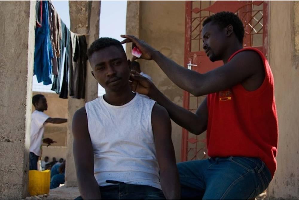Séance de coiffure devant une maison en construction devant le bureau de la direction de l'Etat civil. ©  Morgane Witz
