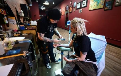 "Tiffany Garcia photographie le ""soundwave tattoo"" d' Hanna Washlake, à Torrance en Californie, le 12 avril 2018 © FREDERIC J. BROWN AFP/Archives"